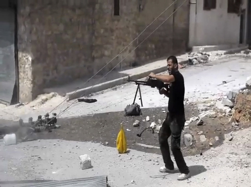 Photo -   In this image made from video and accessed Saturday, Sept. 1, 2012, a Syrian rebel fires his weapon at Syrian Army positions during fighting in Aleppo, Syria. Syrian troops bombarded the northern city of Aleppo Saturday with warplanes and mortar shells as soldiers clashed with rebels in different parts of Syria's largest city, activists said. The Britain-based Syrian Observatory for Human Rights said the clashes were concentrated in several tense neighborhoods where some buildings were damaged and a number of people were wounded. (AP Photo via AP video)