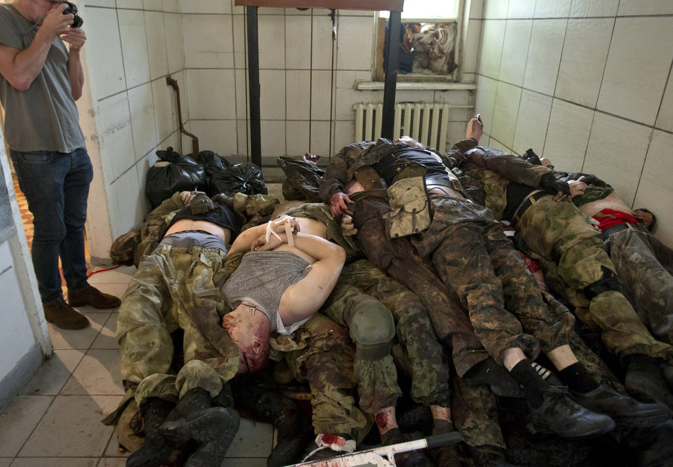 Photo - The bodies of pro-Russian gunmen killed in clashes with Ukrainian government forces around the airport are piled up at a city morgue in Donetsk, Ukraine, Tuesday, May 27, 2014. The eastern city of Donetsk was in turmoil Tuesday a day after government forces used fighter jets to stop pro-Russia separatists from taking over the airport. Dozens were reported killed and the mayor went on television to urge residents to stay indoors. (AP Photo/Vadim Ghirda)