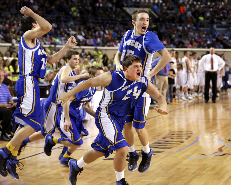 Photo - Glencoe players, including Claytin Beaver, #24, and Ty Lazenby, #35, erupt into celebration as they jump from their chairs and run onto the floor to join in a dog pile of  teammates as time end during Class A boys high school basketball championship game in the Jim Norick Arena at State Fair Park on  Saturday, March 8, 2014. Glencoe defeated Kiowa, 57-39. Photo by Jim Beckel, The Oklahoman