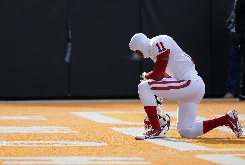 Photo - Oklahoma's Lacoltan Bester (11) kneels for a prayer before the start of the game during the Bedlam college football game between the Oklahoma State University Cowboys (OSU) and the University of Oklahoma Sooners (OU) at Boone Pickens Stadium in Stillwater, Okla., Saturday, Dec. 7, 2013. Photo by Chris Landsberger, The Oklahoman