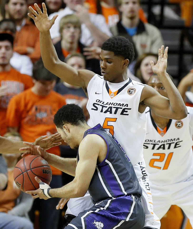 Photo - Oklahoma State's Stevie Clark (5) defends TCU's Kyan Anderson (5) during an NCAA college basketball game between Oklahoma State University (OSU) and TCU at Gallagher-Iba Arena in Stillwater, Okla., Wednesday, Jan. 15, 2014. Oklahoma State won 82-50. Photo by Bryan Terry, The Oklahoman