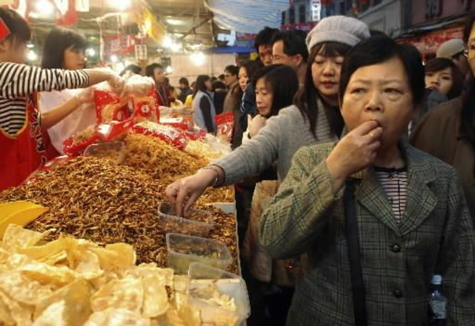 Taiwanese shoppers taste some samples at the Dihua Street market, Saturday, Feb. 6, 2010, in Taipei, Taiwan. Taiwanese shoppers has started hunting for  foods on sale and other bargains at the market ahead of  Chinese Lunar New Year celebrations. The  Chinese New Year falls on Feb. 14 this year and will commemorate the year of the tiger. (AP Photo/Chiang Ying-ying)