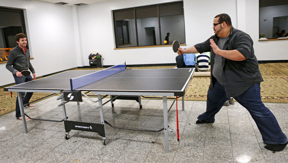 Abdur- Rahman Taleb, the new youth director for the Islamic Society of Greater  Oklahoma City, plays table tennis with volunteer Andrew Stodghill  during youth activities at the Mercy School  complex.