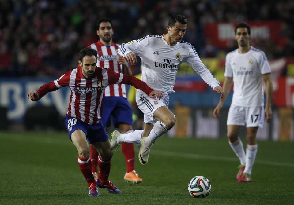 Photo - Atletico's Juanfran, left, in action with Real's Cristiano Ronaldo, centre, during a semi final, 2nd leg, Copa del Rey soccer match between Atletico de Madrid and Real Madrid at the Vicente Calderon stadium in Madrid, Spain, Tuesday, Feb. 11, 2014. (AP Photo/Gabriel Pecot)