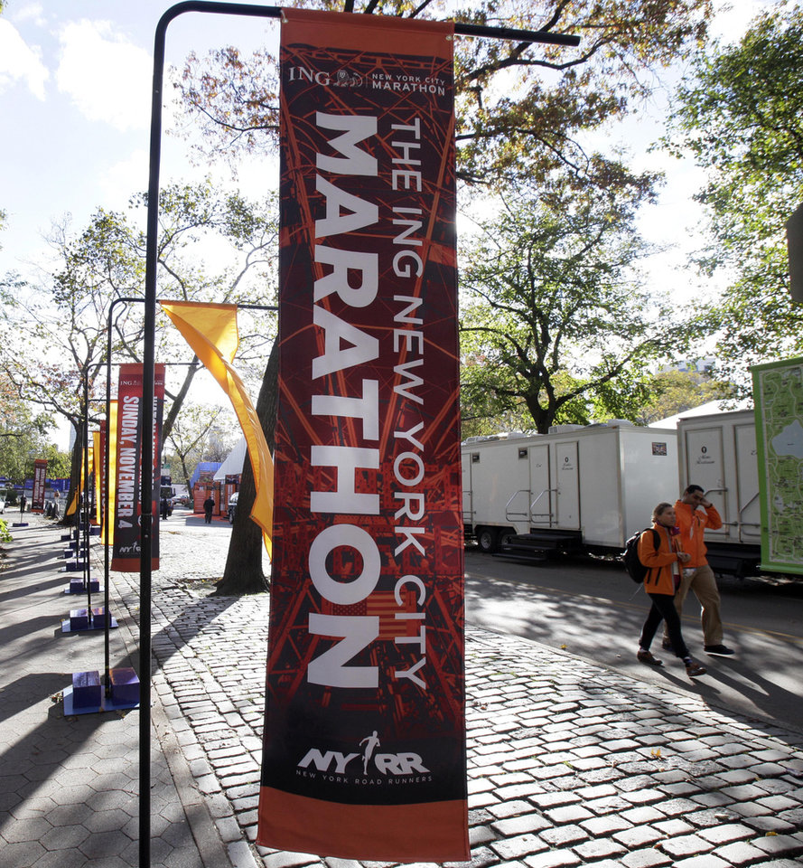 Photo -   New York City Marathon banners adorn an entrance to New York's Central Park, Friday, Nov. 2, 2012. Under growing pressure as thousands still shivered from Sandy, the marathon was canceled Friday by Mayor Michael Bloomberg after mounting criticism that this was not the time for a race. (AP Photo/Richard Drew)