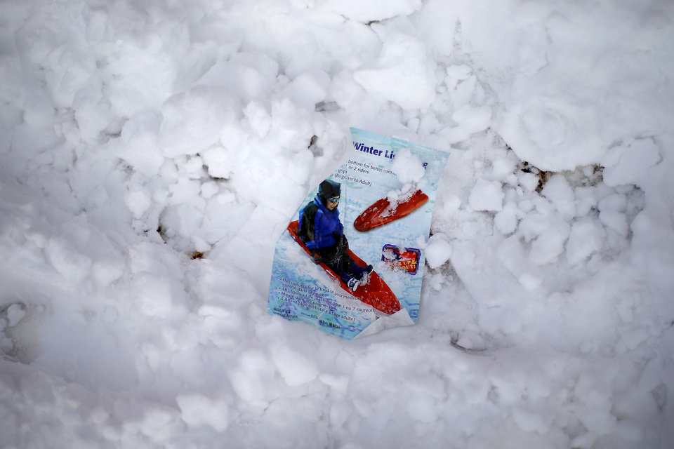 Part of the packaging for a sled is covered in snow outside a northwest Oklahoma City area neighborhood near 164th and Pennsylvania after winter storm moved through the area, Friday, December 6, 2013. Photo by Bryan Terry, The Oklahoman
