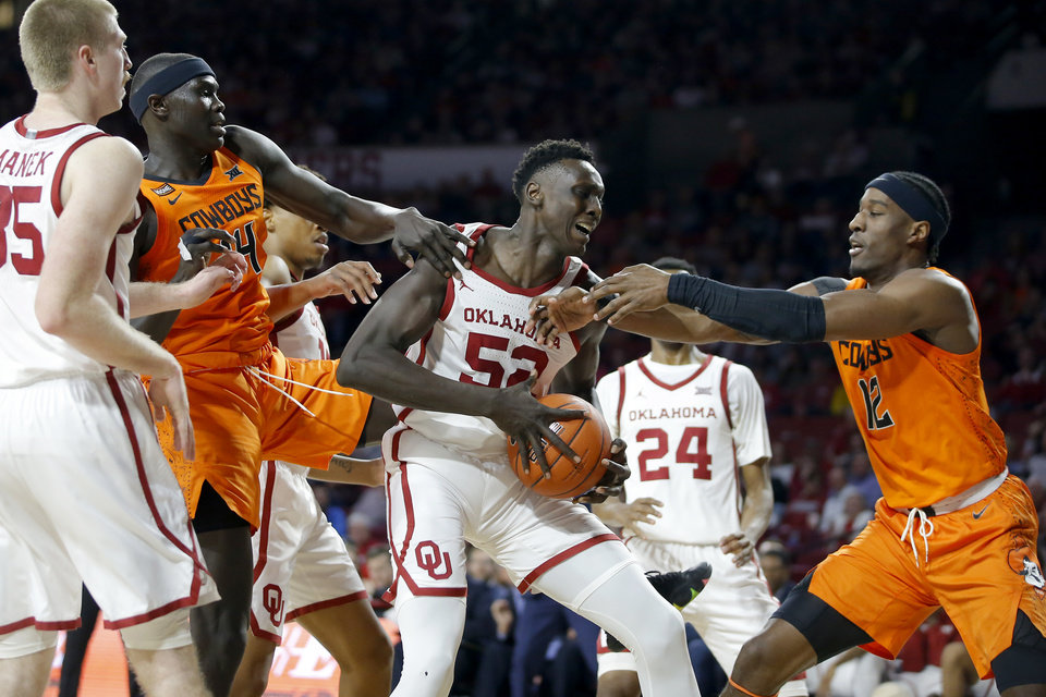 Photo - Oklahoma's Kur Kuath (52) fights for the ball with Oklahoma State's Yor Anei (14)  and Cameron McGriff (12) during a Bedlam college basketball game between the University Oklahoma Sooners (OU) and the Oklahoma State Cowboys (OSU) at the Lloyd Noble Center in Norman, Okla., Saturday, Feb. 1, 2020. [Bryan Terry/The Oklahoman]