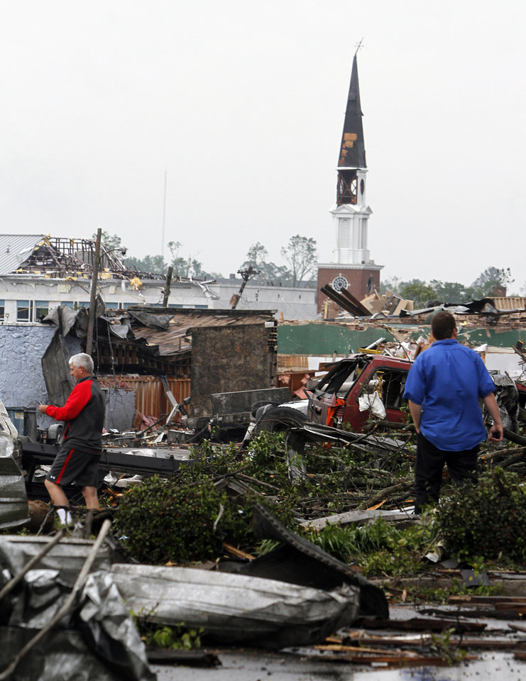 Photo - People walk through downtown after a tornado hits downtown Culman, Ala. on Wednesday, April 27, 2011. A wave of thunderstorms with winds blowing near hurricane force strafed the South on Wednesday, killing at least 16 people from Arkansas to Alabama. (AP Photo/Butch Dill)