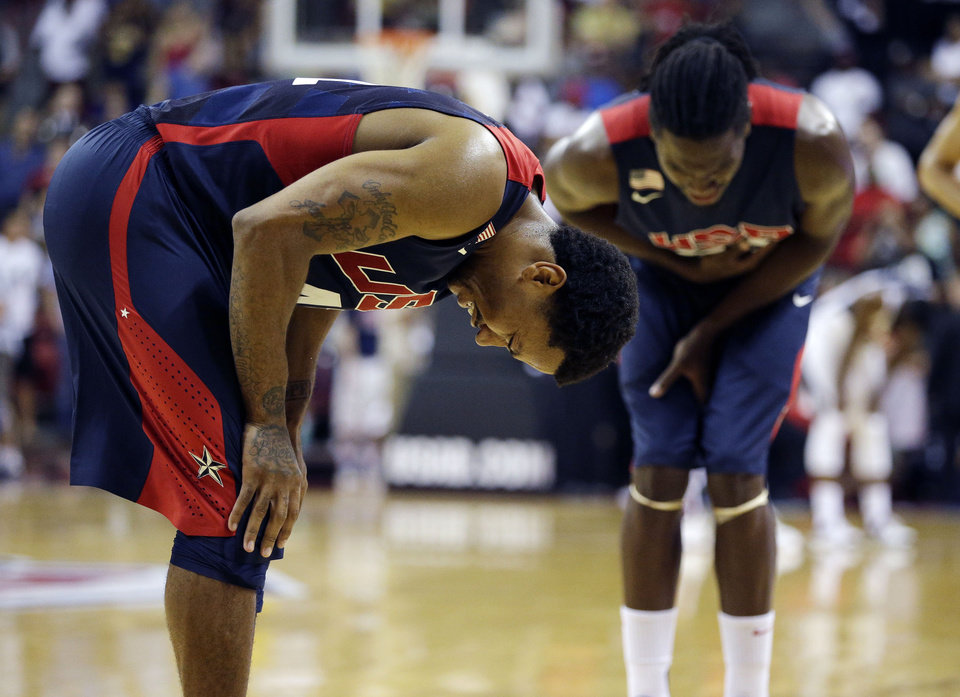 Photo - Chicago Bulls' Derrick Rose, left, and Denver Nuggets' Kenneth Faried, right, react after seeing Indiana Pacers' Paul George get injured during the USA Basketball Showcase game Friday, Aug. 1, 2014, in Las Vegas. (AP Photo/John Locher)