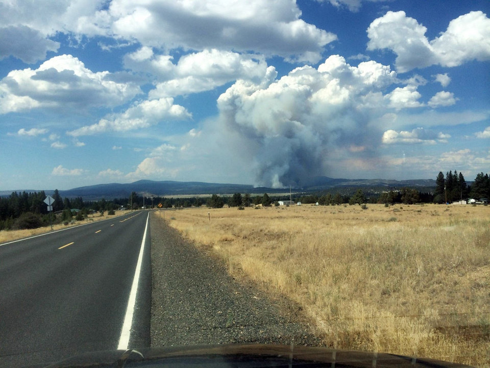Photo - In this photo provided by South Central Oregon Fire Management Partnership, smoke from a fire is seen Sunday, July 13, 2014, near Moccasin Hill, Ore. Officials say a fast-growing wildfire in southern Oregon has destroyed homes and forced dozens of evacuations. (AP Photo/South Central Oregon Fire Management Partnership)