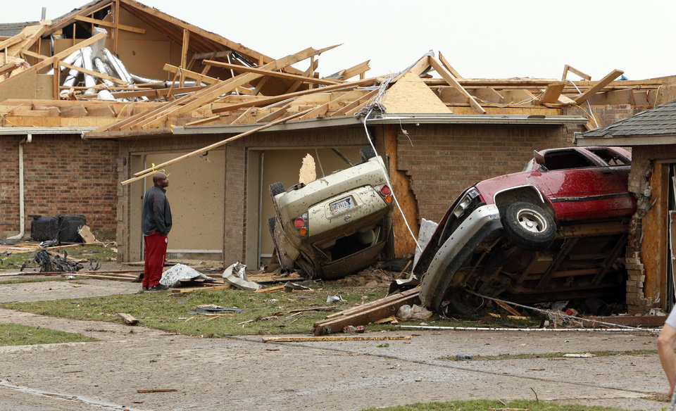 A resident looks at automobiles tossed between houses near SW 149th and Western on Monday, May 20, 2013  in Moore, Okla. Photo by Steve Sisney, The Oklahoman