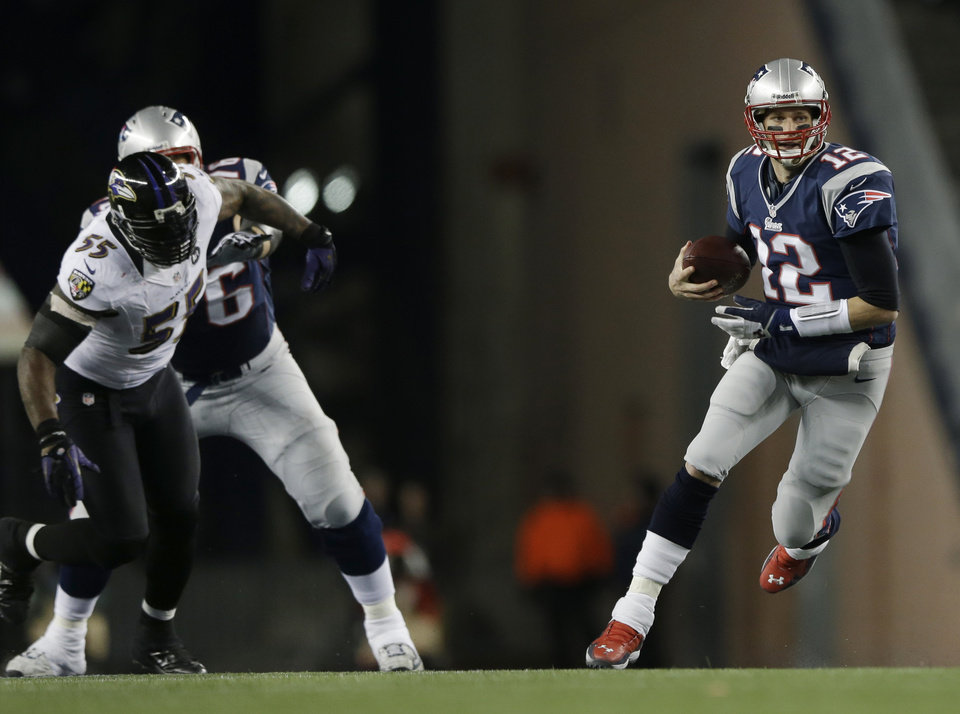 Photo - New England Patriots quarterback Tom Brady, right, runs with the ball while being chased by Baltimore Ravens linebacker Terrell Suggs (55) during the first half of the NFL football AFC Championship football game against the Baltimore Ravens in Foxborough, Mass., Sunday, Jan. 20, 2013. (AP Photo/Matt Slocum)