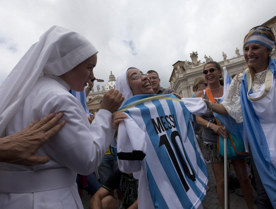 Photo - Argentine nuns show an Argentina soccer team jersey with the name and number of Lionel Messi before Pope Francis delivers the Angelus prayer in St. Peter square at the Vatican, Sunday, July 13, 2014. The Argentine-born, football-loving pontiff pledged neutrality, promising not to pray for any team. However, Francis did tweet on the eve of the final: