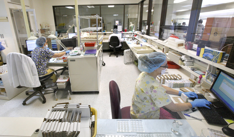 Photo -  Extract lab technicians fill prescriptions from allergy extract bottles in a controlled room in the extract lab May 6 at the Oklahoma Allergy and Asthma Clinic in Oklahoma City. Photo by Paul B. Southerland, The Oklahoman   PAUL B. SOUTHERLAND -