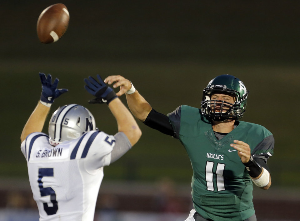 Photo - Edmond Santa Fe's Justice Hansen throws the ball as Edmond North's Sam Brown defends during high school football game between Edmond Santa Fe and Edmond North at Wantland Stadium in Edmond, Okla.,  Friday, Sept. 14, 2012. Photo by Sarah Phipps, The Oklahoman
