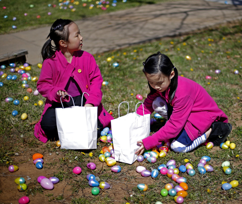 Photo -   At left:  Elizabeth Ting, 8, left, and Elaine Ting, 6, collect eggs during New Covenant United Methodist Church's Easter Egg Hunt and spring carnival in March. [PHOTO BY BRYAN TERRY, THE OKLAHOMAN]
