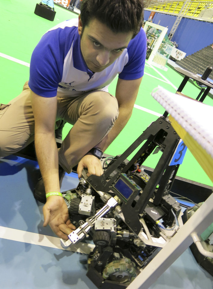 Photo - In this photo taken Thursday, June 27, 2013 Mostafa Mahmoodi, in charge of mechanical systems for the robotics team from Iran's Qazvid Islamic Open University, shows off the kicking and passing device used by his mid-sized robots at the RoboCup in Eindhoven, Netherlands. Around 300 teams from 40 countries are competing this week in the RoboCup championships. The competition has the long-term goal of building a team of androids good enough to beat the human world cup team by 2050. (AP Photo/Toby Sterling)