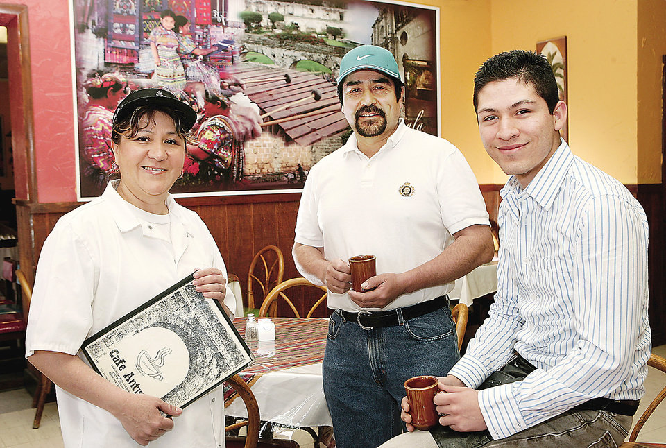 Photo - From left, Elida Valdez, Benjamin Valdez and Luidgi Del Cid stand inside Cafe Antigua, 1903 Classen Blvd. PHOTOS BY JIM BECKEL, THE OKLAHOMAN