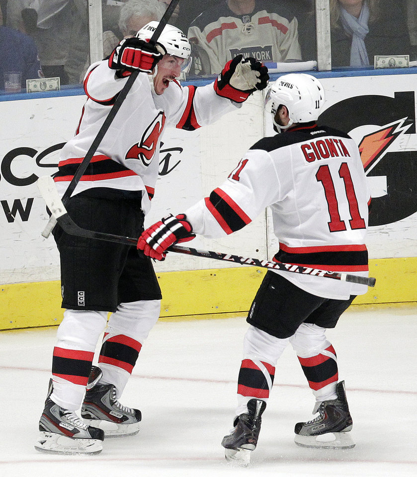 Photo -   New Jersey Devils' Ryan Carter, left, celebrates with Stephen Gionta after Carter's goal during the third period of Game 5 of an NHL hockey Stanley Cup Eastern Conference final playoff series against the New York Rangers, Wednesday, May 23, 2012, in New York. The Devils won 5-3. (AP Photo/Julio Cortez)