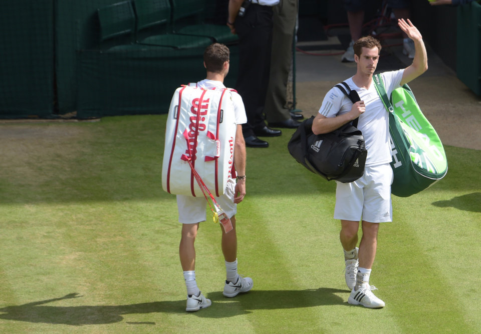 Photo - Defending champion Andy Murray of Britain waves as he leaves centre court after being defeated by Grigor Dimitrov of Bulgaria, left, in their men's singles quarterfinal match at the All England Lawn Tennis Championships in Wimbledon, London, Wednesday July 2, 2014. (AP Photo)