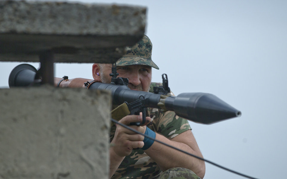 Photo - A pro-Russian rebel prepares to fire a rocket propelled grenade on the rooftop of an apartment building during clashes during clashes as they attack a border guard base held by Ukrainian troops on the outskirts of Luhansk, eastern Ukraine, Monday, June 2, 2014. Some hundreds of pro-Russia insurgents attacked the base on Monday, with some firing rocket-propelled grenades from the roof of a nearby residential building. At least five rebels were killed when the guards returned fire, a spokesman for the border guard service said. (AP Photo/Vadim Ghirda)