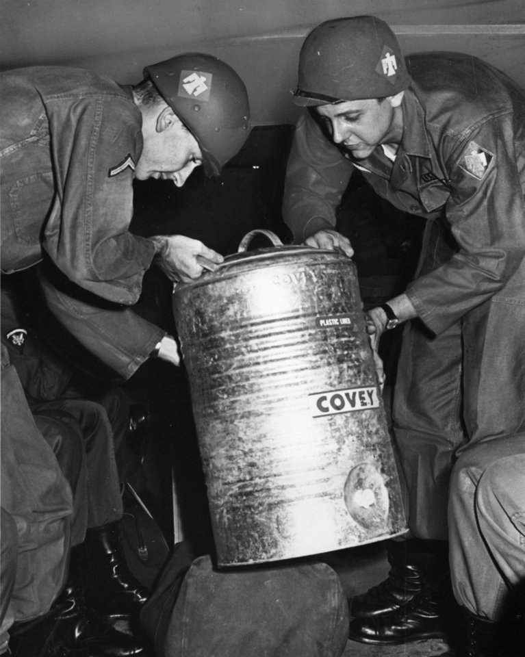 Photo -  Necessity of life is water, even for soldiers, so Oklahoma City Thunderbirds, who started two-week encampment at Fort Chaffee, Ark. Saturday carried watercans on convoy.  Here Von Nemecek and James Jorski unload can.  Staff photo by Austin Traverse.  Photo dated 08/01/1964 and published on 08/02/1964 in The Daily Oklahoman.