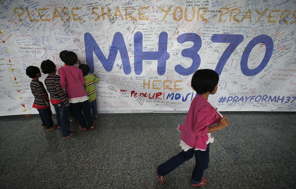 Photo - Children read messages and well wishes displayed for all involved with the missing Malaysia Airlines jetliner MH370 on the walls of the Kuala Lumpur International Airport, Thursday, March 13, 2014 in Sepang, Malaysia. Planes sent Thursday to check the spot where Chinese satellite images showed possible debris from the missing Malaysian jetliner found nothing, Malaysia's civil aviation chief said, deflating the latest lead in the six-day hunt. The hunt for the missing Malaysia Airlines flight 370 has been punctuated by false leads since it disappeared with 239 people aboard about an hour after leaving Kuala Lumpur for Beijing early Saturday. (AP Photo/Wong Maye-E)