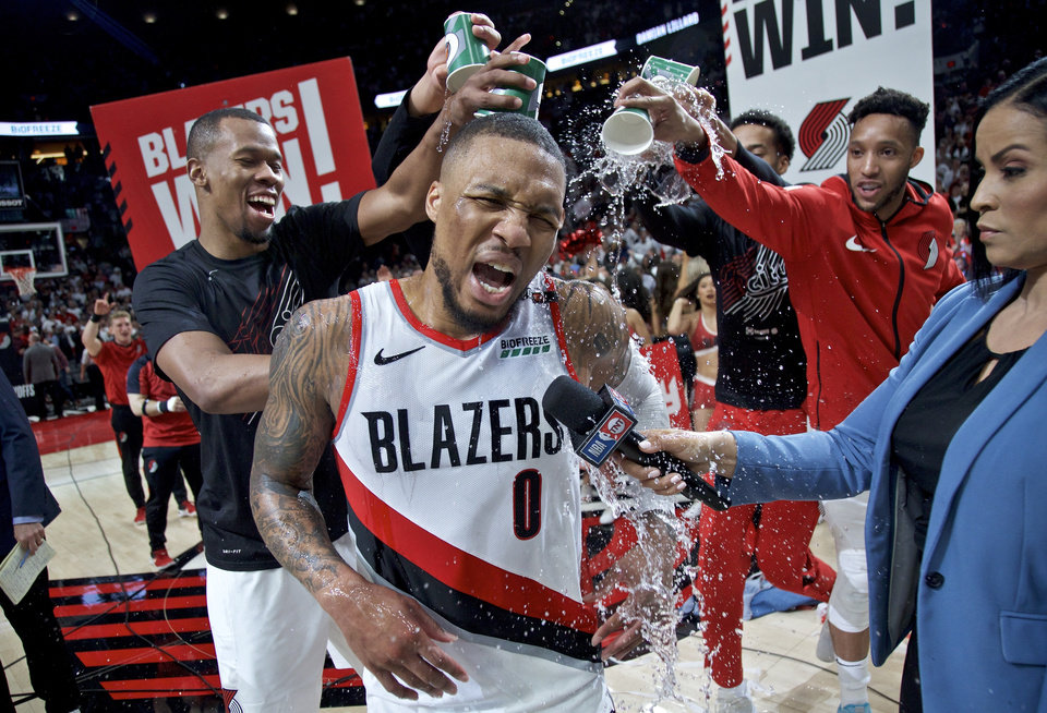 Photo - Portland Trail Blazers' Damian Lillard (0) gets water poured on him by teammates Rodney Hood, left, and guard Evan Turner, right, after Game 5 of an NBA basketball first-round playoff series against the Oklahoma City Thunder, Tuesday, April 23, 2019, in Portland, Ore. The Trail Blazers won 118-115. (AP Photo/Craig Mitchelldyer)
