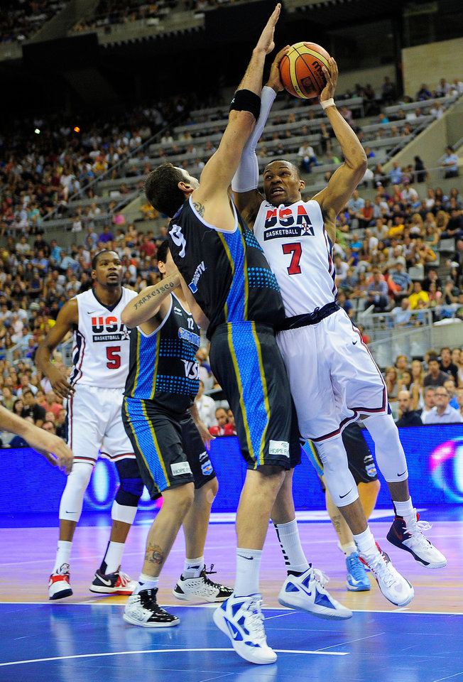 Russell Westbrook of the US Men's Senior National Team, right, dives for the ball against Juan Gutierrez of the Argentina Men's Senior National Team during their Pre-Olympic friendly basketball match at the Palau Sant Jordi in Barcelona, Spain, Sunday, July 22, 2012. (AP Photo/Manu Fernandez) ORG XMIT: MF105