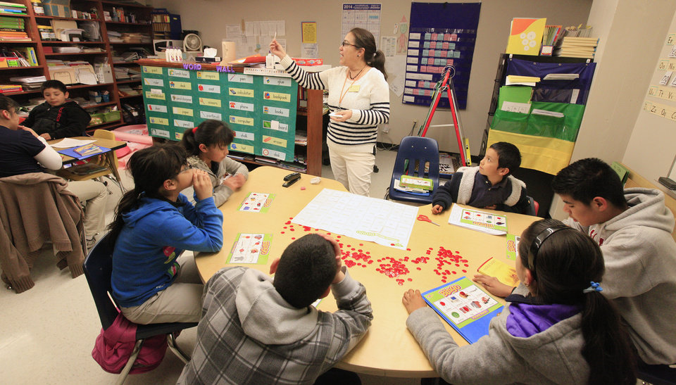 Photo - English language learner instructor Patricia Trotter works with second- through sixth-graders Wednesday on a reading exercise during intersession at Herronville Elementary School in Oklahoma City.  Photo by Paul B. Southerland, The Oklahoman  PAUL B. SOUTHERLAND - PAUL B. SOUTHERLAND