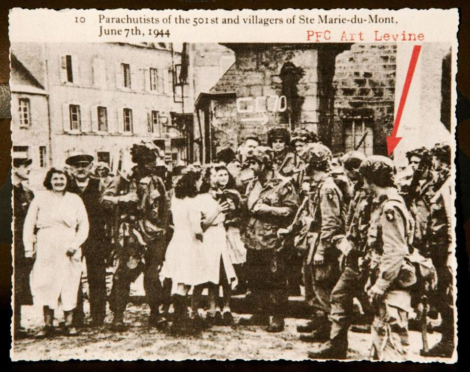 This photograph taken on June 7, 1944 shows  PFC Art Levine (far right) with other soldiers from the 501st regiment of the 101st Division being welcomed by townspeople in the French village of Ste. Marie-du-Mont after American forces drove German troops from the city. Levine said only a few hours after this photo was taken, a German sniper killed the soldier in the center of the photo, talking to the women.  Levine isolated the building where the sniper fire came from and went into the building, tossed a grenade in a room where he was hiding, killing the German soldier.