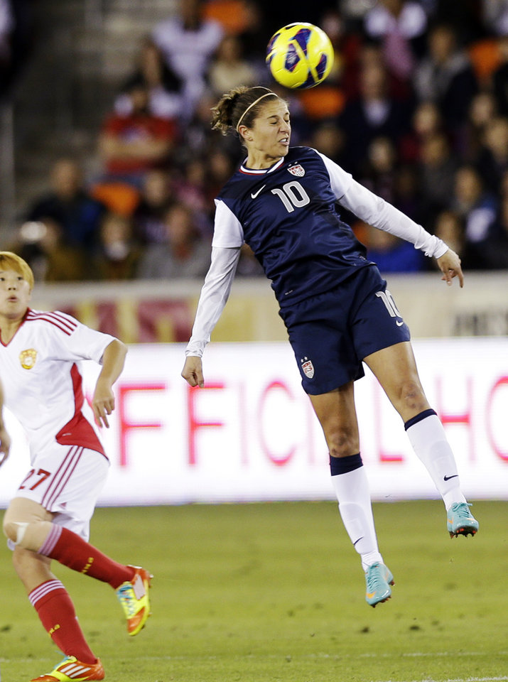 United States' Carli Lloyd (10) heads the ball in front of China's Li Ying during the first half of an exhibition soccer match, Wednesday, Dec. 12, 2012, in Houston. (AP Photo/David J. Phillip)