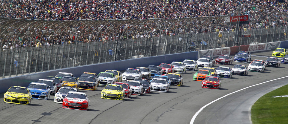 Photo - The field heads for Turn 1 at the start of the NASCAR Sprint Series auto race in Fontana, Calif., Sunday, March 23, 2014. (AP Photo/Alex Gallardo)
