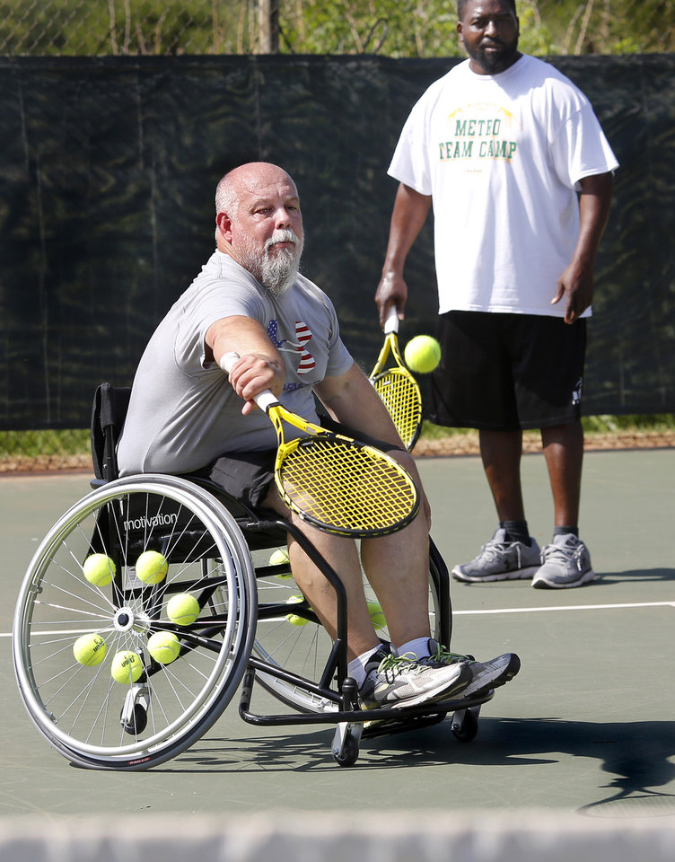 Photo -  Paul Horton returns a serve at the veteran's wheelchair tennis clinic. [PHOTO BY JIM BECKEL, THE OKLAHOMAN]