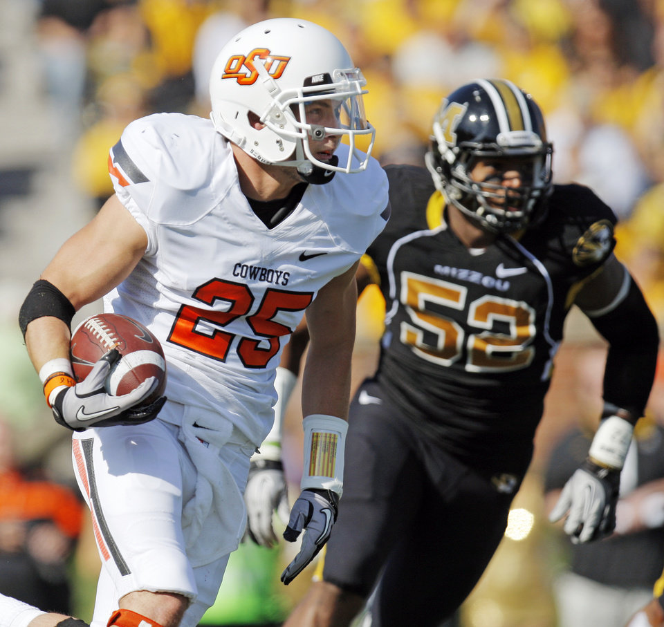Photo - Oklahoma State's Josh Cooper (25) carries the ball as Missouri's Michael Sam (52) pursues in the first quarter during a college football game between the Oklahoma State University Cowboys (OSU) and the University of Missouri Tigers (Mizzou) at Faurot Field in Columbia, Mo., Saturday, Oct. 22, 2011. Photo by Nate Billings, The Oklahoman
