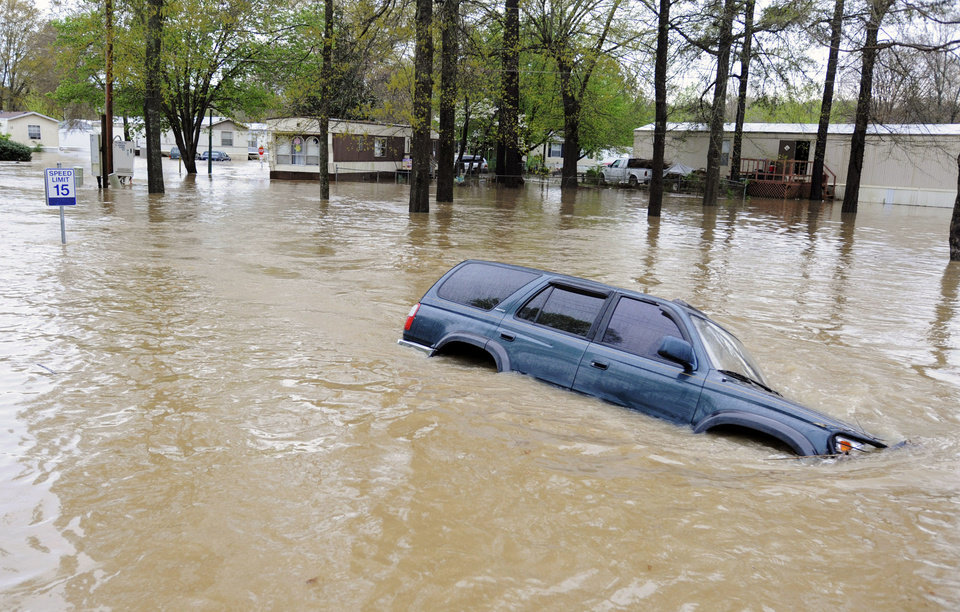 Photo - An abandoned vehicle sits submerged by floodwaters on a road in a mobile home park in Pelham, Ala., on Monday, April 6, 2014. Storms dumped torrential rains in central Alabama overnight, causing flooding across the region. (AP Photo/Jay Reeves)