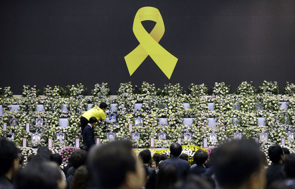 Photo - A worker arranges a portrait of a victim of the sunken ferry Sewol, at a memorial altar in Ansan, south of Seoul, South Korea, Wednesday, April 30, 2014. Two weeks after the ferry sank off South Korea's southern cost, divers have recovered scores of bodies from the wreckage, but they fought strong currents and floating debris inside the ship Wednesday as they searched for the rest of the passengers still missing. (AP Photo/Lee Jin-man)