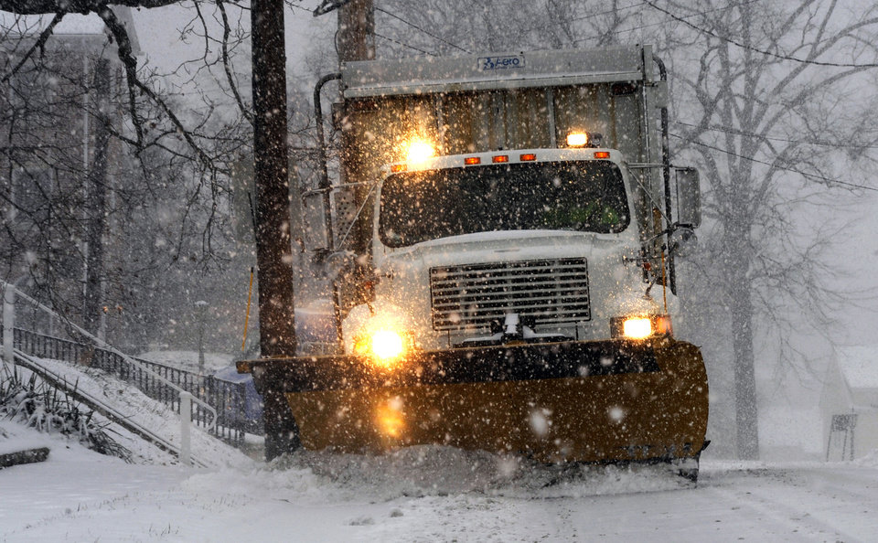 Photo - A snow plow removes snow from New Windsor Road as snow falls, Tuesday, Jan. 21, 2014, in Westminster, Md. (AP Photo/Carroll County Times, Ken Koons)