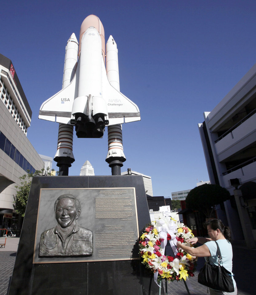Photo - Lisa Shimamoto places flowers in 2011 on a Challenger space shuttle memorial in Los Angeles for USAF Col. Ellison Onizuka, the first Japanese American astronaut, who died along with six other crew members when the Challenger exploded just after launching. (AP Photo/Nick Ut)