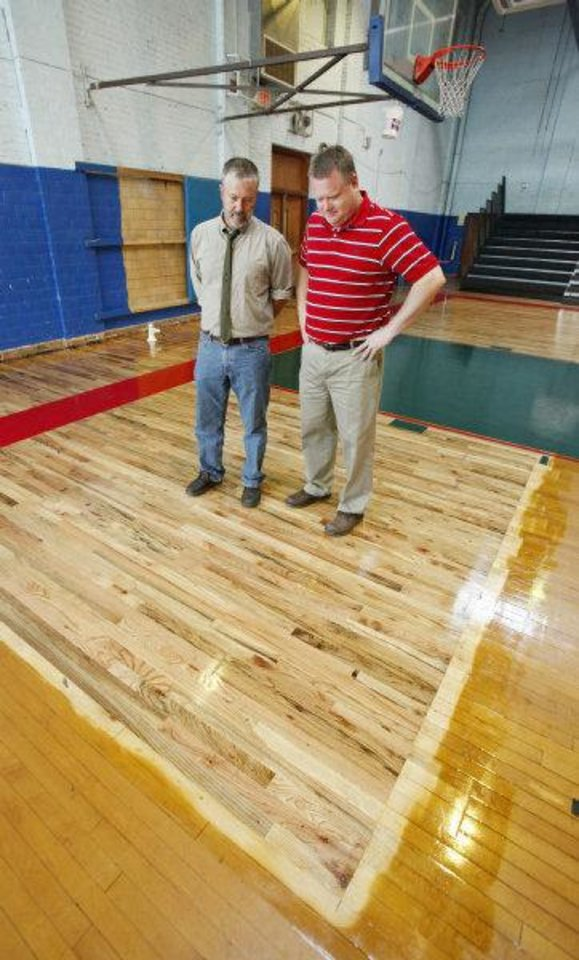 Photo - The Rev. Robin Meyers, senior pastor of Mayflower United Church of Christ, and Eric Schellenger, Taft Middle School principal, looking at a section of the school's gym floor that was recently replaced by a member of Mayflower.   PAUL B. SOUTHERLAND - PAUL B. SOUTHERLAND