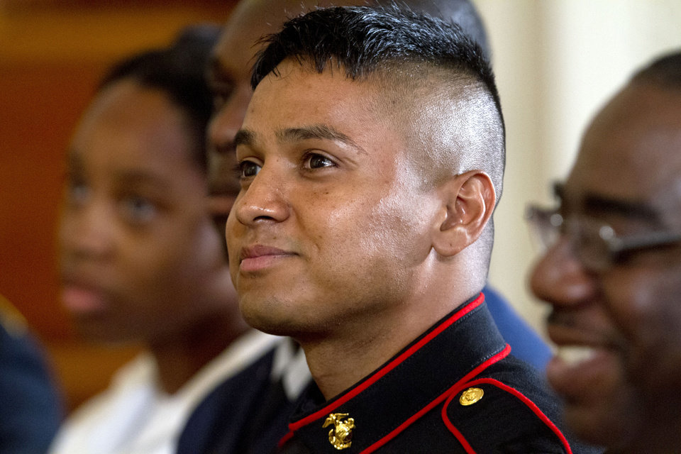 Photo - Marine Private First Class Oscar Gonzalez, who was born in Guatemala, listens as President Barack Obama speaks during a naturalization ceremony for active duty service members, including Gonzalez, and civilians, Friday, July 4, 2014, in the East Room of the White House in Washington. Obama highlighted a positive side of the immigration debate by presiding over an Independence Day citizenship ceremony for service members who signed up to defend the U.S. even though they weren't American citizens. (AP Photo/Jacquelyn Martin)