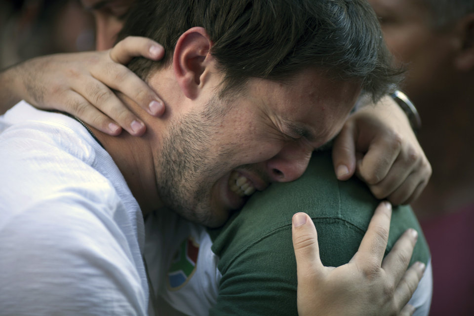 Photo - A man cries during a protest near the Kiss nightclub where a fire killed over 230 people in Santa Maria, Brazil, Tuesday, Jan. 29, 2013. The blaze began at around 2:30 am local time on Sunday, during a performance by Gurizada Fandangueira, a country music band that had made the use of pyrotechnics a trademark of their shows. (AP Photo/Felipe Dana)