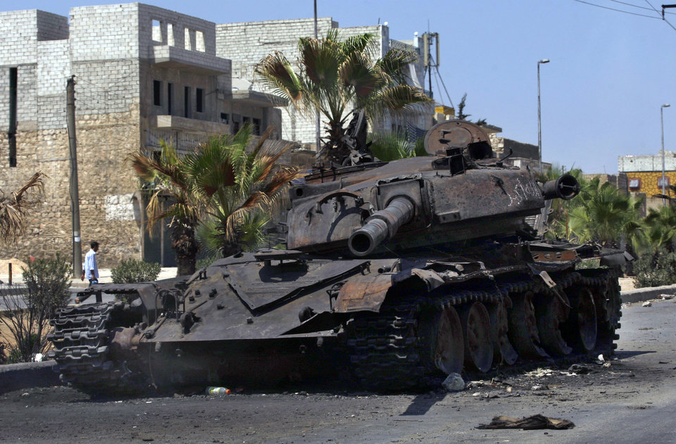 Photo -   The remains of a destroyed military tank is seen on a street in the town of Hanano in Aleppo, Syria, Friday, Aug. 17, 2012. Rebel footholds in Aleppo have been the target of weeks of Syrian shelling and air attacks as part of wider offensives by President Bashar Assad's regime. Rebels have been driven from some areas, but the report of clashes near the airport suggests the battles could be shifting to new fronts. (AP Photo/ Khalil Hamra)