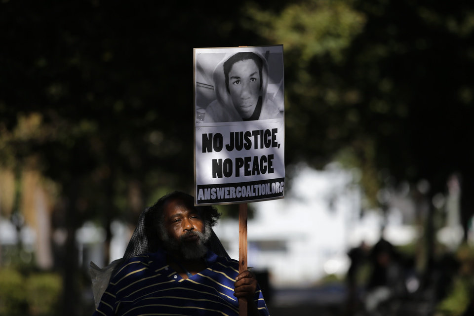 Photo - John Simpson, 56, carries a sign showing an image of Trayvon Martin during a demonstration in reaction to the acquittal of neighborhood watch volunteer George Zimmerman on Monday, July 15, 2013, in Los Angeles. Anger over the acquittal of the U.S. neighborhood watch volunteer who shot dead an unarmed black teenager continued Monday, with civil rights leaders saying mostly peaceful protests will continue this weekend with vigils in dozens of cities. (AP Photo/Jae C. Hong)