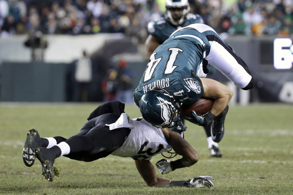 Photo - Philadelphia Eagles' Riley Cooper, right, is upended on a hit by New Orleans Saints' Rod Sweeting during the second half of an NFL wild-card playoff football game, Saturday, Jan. 4, 2014, in Philadelphia. (AP Photo/Matt Rourke)