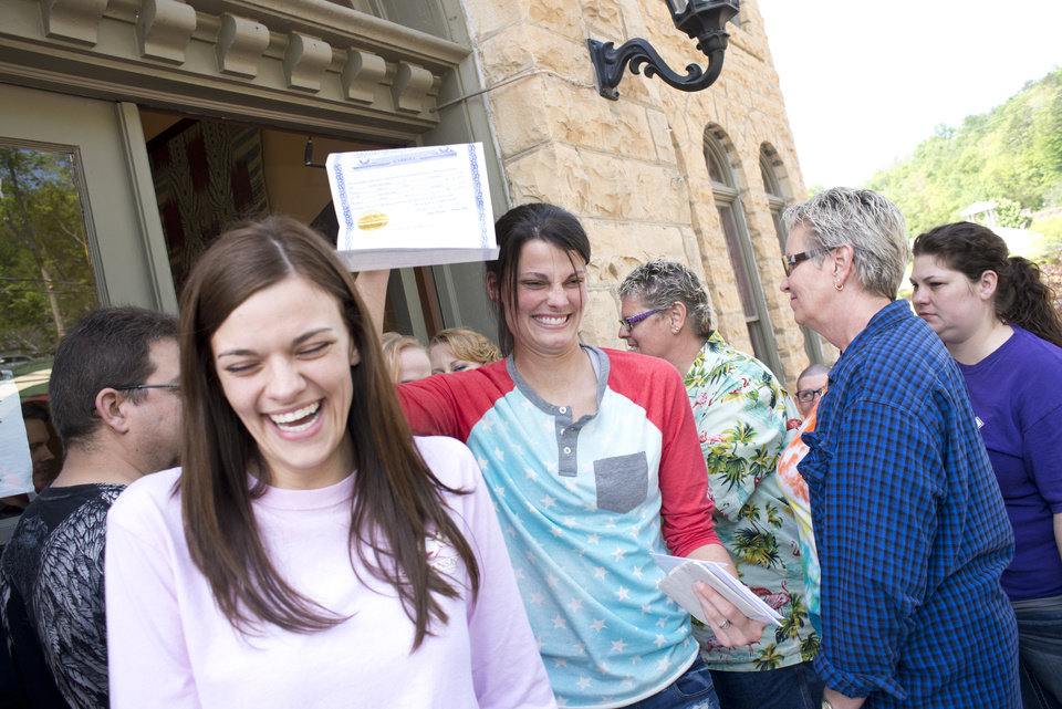 Photo - Kristin Seaton, center, of Jacksonville, Ark., holds up her marriage license as she leaves the Carroll County Courthouse in Eureka Springs, Ark., with her partner, Jennifer Rambo, left, of Fort Smith, Ark. Saturday, May 10, 2014, in Eureka Springs, Ark. Rambo and Seaton were the first same-sex couple to be granted a marriage license in Eureka Springs after a judge overturned Ammendment 83, which banned same-sex marriage in the state of Arkansas. (AP Photo/Sarah Bentham)