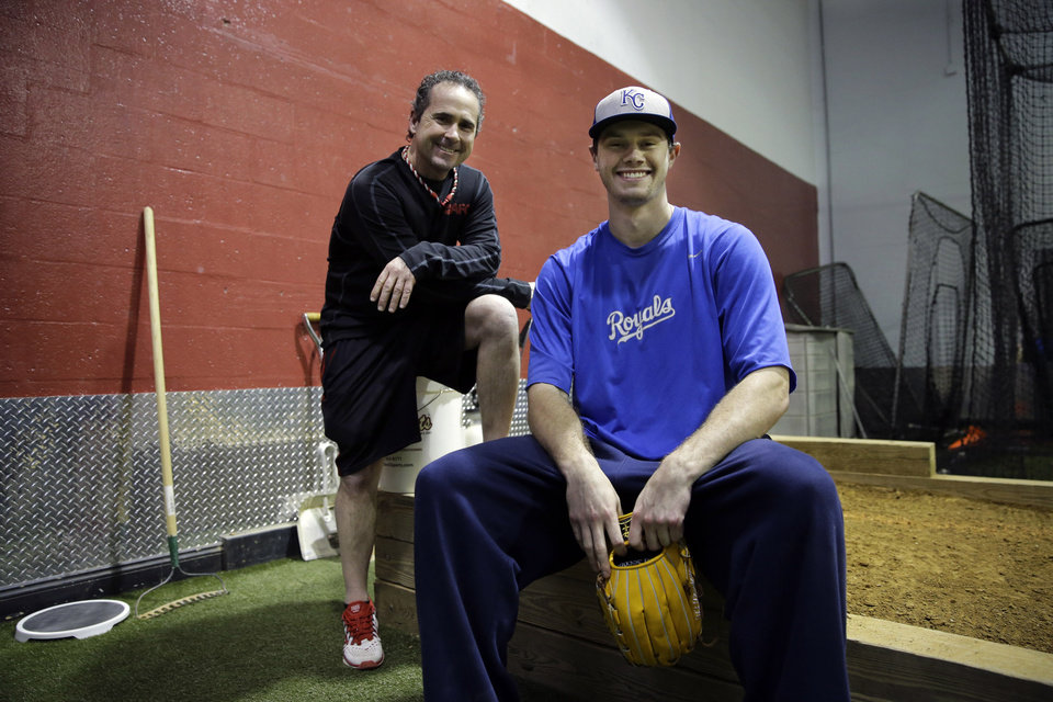 Photo - In this Feb. 24, 2014 photo, Kansas City Royals minor league pitcher,  John Walter, of Haddonfield, N.J., poses for a photo at Power Train Sports Institute's AFC Baseball & Softball Academy, with Program Director Rob Potts. Potts is a 55-year-old former postal worker who spends his summers throwing batting practice to Chase Utley, Jimmy Rollins and Ryan Howard. When he's not at the ballpark, he's director of baseball operations at the baseball facility where several major and minor leaguers not only stay in shape during the winter, but hold pitching clinics for kids.  (AP Photo/Mel Evans)