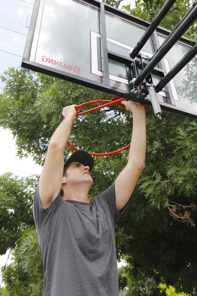 Photo - J. J. Gourley, Westminster Presbyterian Church deacon, puts together a basketball goal donated to a family raising foster children.  PAUL B. SOUTHERLAND -  PAUL B. SOUTHERLAND