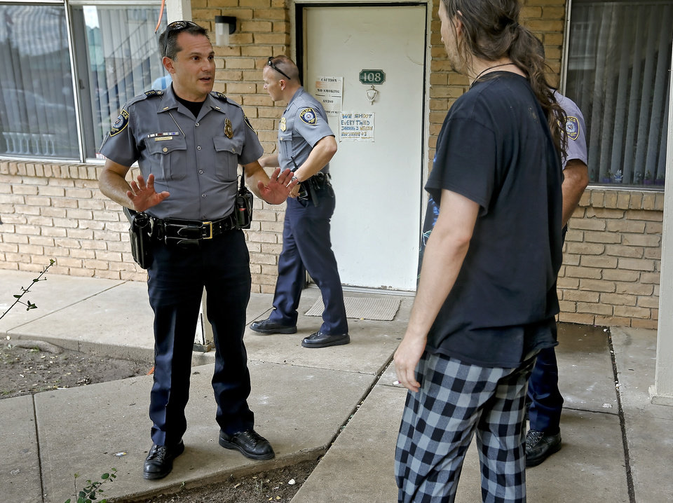 Photo -  Oklahoma City police Hefner Patrol Division's Isaac Goodman talks to residents while working foot patrol Tuesday at the Windsor Village Apartments in Oklahoma City. The division has been on a yearlong initiative to cut back the violence around the area in northwest Oklahoma City. Photo by Chris Landsberger, The Oklahoman      -