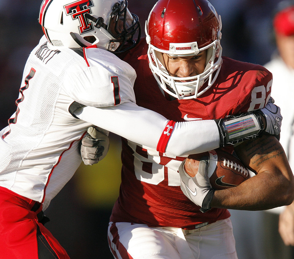 Photo - Oklahoma's James Hanna (82) runs through Texas Tech's Terrance Bullitt (1) during the first half of the college football game between the University of Oklahoma Sooners (OU) and the Texas Tech Red Raiders (TTU) at the Gaylord Family Memorial Stadium on Saturday, Nov. 13, 2010, in Norman, Okla.  Photo by Chris Landsberger, The Oklahoman